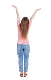 Back view of Beautiful woman in jeans looking at wall and Holds Stock Photography
