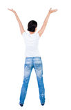 Back view of Beautiful woman in jeans looking at wall and Holds Royalty Free Stock Images