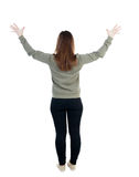 Back view of Beautiful woman looking at wall and Holds  hand up. Stock Images