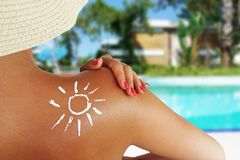 Back view of a beautiful woman taking care about her skin at swimming pool, sun protection concept stock photo