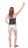 Back view of beautiful woman welcomes. Young teenager girl in shorts hand waving from. Rear view  people collection.  backside view of person.  Isolated over Stock Photos