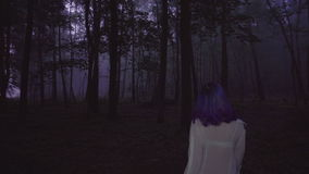 Back view of beautiful woman in white shirt and purple hair walking in dark forest - thriller scene.  stock footage