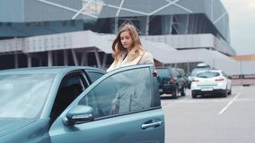 Back view of a beautiful young European girl with a long hair, in a warm coat using the remote control to unlock the. Alarm system of a luxurious car, and stock video footage
