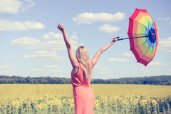 Back view of beautiful young lady holding multicolored umbrella in sunflower field and blue sky outdoors. Royalty Free Stock Image