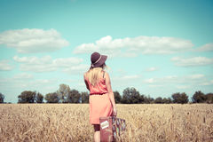 Back view of beautiful young lady with suitcase on countryside landscape outdoors background royalty free stock photography