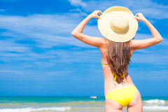 Back view of beautiful young woman in bikini and. Hat standing on tropical beach enjoying the sun. This image has attached release Stock Photography