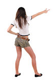 Back view of beautiful young woman pointing at wall Royalty Free Stock Photo