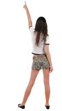 Back view of beautiful young woman in shorts pointing at wal Royalty Free Stock Photos