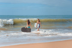 Back view of beautiful young women with surfboards. Picture of beautiful young women with surfboards entering sea. Back view of pretty girls on blurred seascape Stock Photography