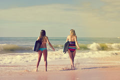 Back view of beautiful young women walking away. Picture of beautiful young women walking away with surfboards. Back view of pretty girls on blurred seascape Royalty Free Stock Photos