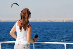 Back view of beholding young woman. On yacht looking on the sea Stock Image