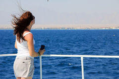 Back view of beholding young woman. On yacht looking on the sea Royalty Free Stock Photography