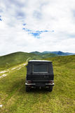 Back view of black terrain car on pasture Stock Photography