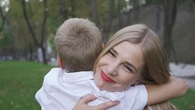 Back view of blond boy running towards his mother. Attractive young woman hugging her son and smiling. Happy family stock footage