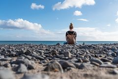 Back view of blond caucasian woman sitting cross-legged on natural pebble beach. Back view of blond caucasian woman with leather backpack sitting cross-legged on Stock Photos