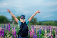 Back view. blonde girl in a sports T-shirt, baseball cap, with a backpack goes in for sports on a flower field, raised her hands