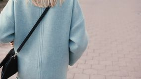 Back view blonde girl wearing fashionable clothes. Glamour woman walking in the street. Fashion industry. Steadicam. Back view blonde girl wearing fashionable stock video