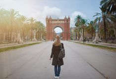 Back view of blonde woman with Arc de Triomf in Barcelona in background. Back view of woman with Arc de Triomf in Barcelona in background Stock Photos