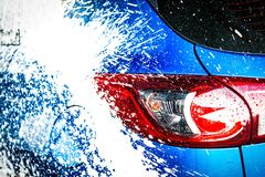 Car washing with soap. Car covered with white foam. Car care service business concept. Royalty Free Stock Photo