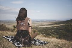 Back view of the Boho girl on a hill looking far in the distance. Back view of the Boho girl on the hill looking far in the distance. Copy space. Horizontal stock image