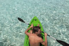 Young happy man kayaking on a tropical island in the Maldives. Clear blue water royalty free stock photography