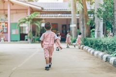 Back view of Boy followed girl friends on street to go to the classroom. In school royalty free stock photography