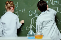 Back view of boy and girl in lab coats drawing chemical formulas on chalkboard. Science school concept stock photos