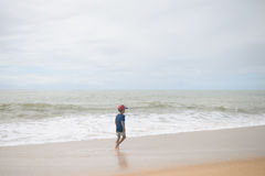 Back view of boy walking along the beach outside during sunset. Back view of boy walking along the beach during sunset outside royalty free stock images