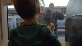 Back view of boy watching in window from rail train and saying goodbye his grandparents, swinging arms stock footage