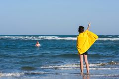 Back view on the boy in the yellow towel standing on seashore and waving his hand to landing plane. Travel. Concept stock photos