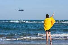 Back view on the boy in the yellow towel standing on seashore and waving his hand to landing plane. Travel Concept royalty free stock image