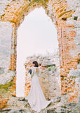 The back view of the bride with the bouwut near the ruins. royalty free stock photo
