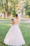 The back view of the bride holding the yellow wedding bouquet at the background of the park. Stock Images