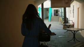Back view of a brunette girl with long hair walking with a bike through a tunnel, slow mo, steadicam shot stock video