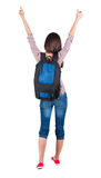 Back view of brunette woman with backpack thumbs up. Stock Image