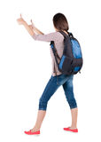 Back view of brunette woman with backpack thumbs up. Stock Photos