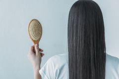 Back view of brunette woman holding hairbrush with fallen hair. Isolated on grey royalty free stock images
