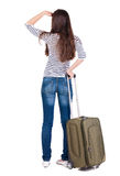Back view of brunette woman with suitcase looking up Stock Image