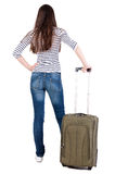 Back view of brunette woman with suitcase looking up Royalty Free Stock Photo