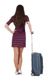 Back view of brunette woman with suitcase looking up Royalty Free Stock Images