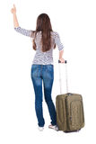 Back view of brunette woman with suitcase thumbs up Royalty Free Stock Images