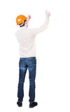 Back view of builder in helmet shows thumbs up. Stock Photo