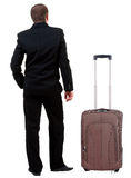 Back view of business man in black suit traveling with suitcas . Royalty Free Stock Images