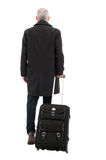 Back view of business man with carry on luggage. Back view of middle age business man holding carry on luggage isolated on white background Stock Photos