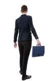 back view of a business man holding a briefcase and walking forward onwhite background stock photos