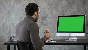 Business man in the office having breakfast, lunch and watching something on the mac, computer. Green Screen Mock-up