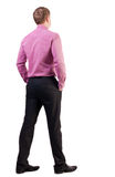Back view of business man  in red shirt looks ahead. Royalty Free Stock Photography