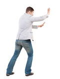 Back view of business man pushes wall. Isolated over white background. Rear view people collection. backside view of person.  Bearded man ran into an obstacle Royalty Free Stock Photos