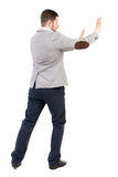 Back view of business man pushes wall. Isolated over white background. Rear view people collection. backside view of person. A guy in a jacket hands in front Stock Photo