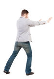 Back view of business man pushes wall. Isolated over white background. Rear view people collection. backside view of person. A guy in a gray jacket waving his Stock Images